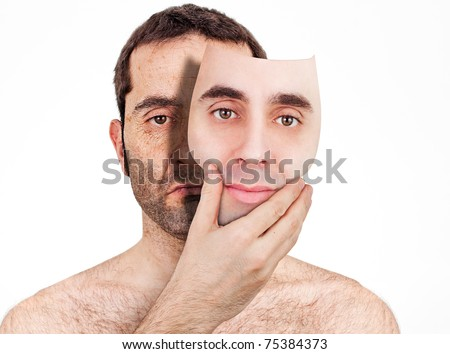 An (apparently) handsome young man removes his face as a mask, revealing and old, ugly and wrinkled face underneath. - stock photo