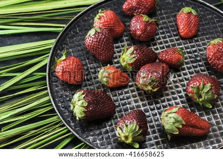 An appetizing strawberry on a black iron plate - stock photo