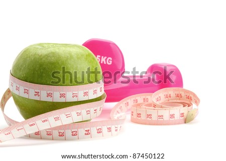 An apple, a measuring tape and dunbbell - stock photo