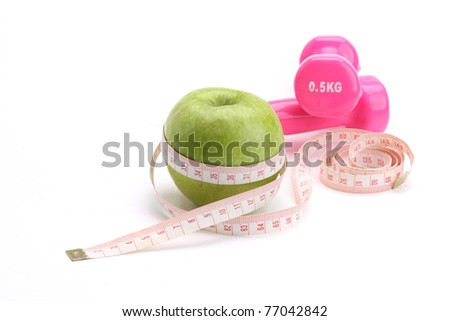 An apple, a measuring tape and dunbbells - stock photo