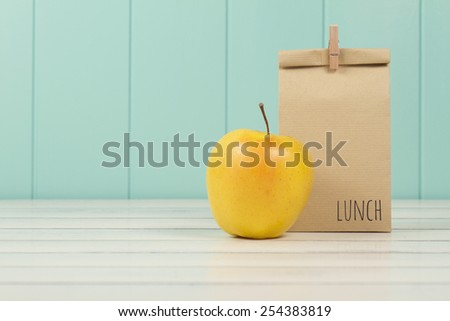 An apple and a paper bag with lunch on a white wooden table with a robin egg blue wainscot. Vintage Style. - stock photo