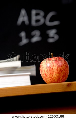 An apple and a stack of books on the teachers desk - stock photo