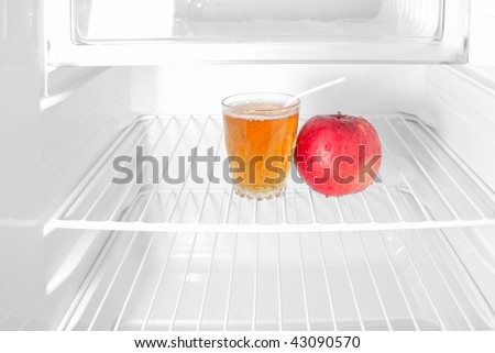 An apple and glass of juice in empty refrigerator as diet symbol. Colored ingredients on black and white background. - stock photo
