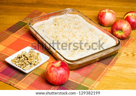 An apple cake with a plate of walnuts and apples - stock photo