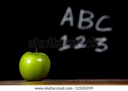 An apple on a desk in the classroom - stock photo