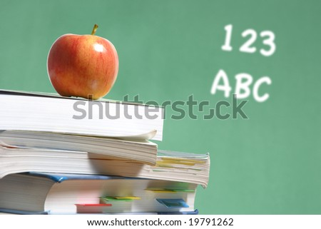 An apple on a stack of books on the teachers desk - stock photo