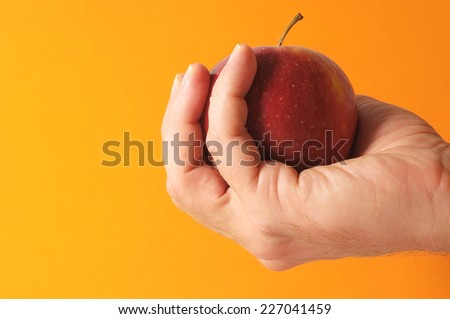 An Apple on the Hand on a Colored Background - stock photo