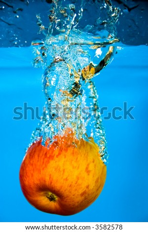 An apple plunged into cool blue water - stock photo