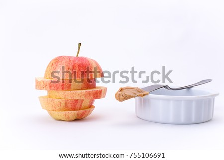 An apple stacked in slices and a knife with peanut butter on a bowl.
