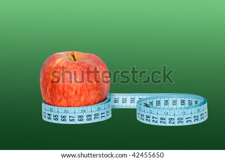 An apple with measuring tape isolated on green background - stock photo