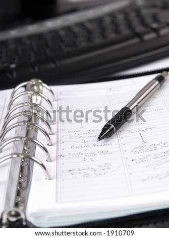 An appointment book in front of a computer - stock photo