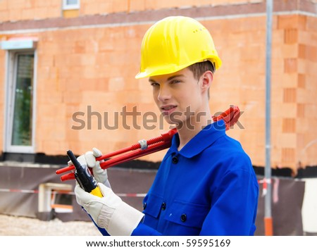 An apprentice / trainee. Construction workers on site with a helmet.
