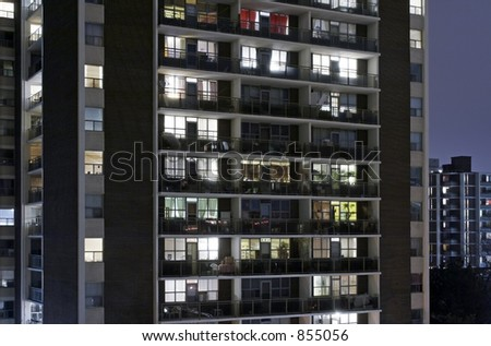 An aprtment building at night with lights. - stock photo