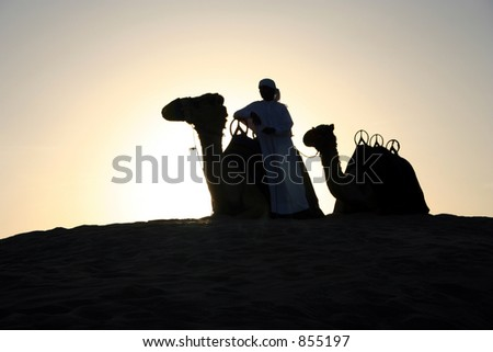 An Arab Camel Herder pauses for a rest at sunset - stock photo