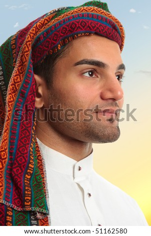 An arab middle eastern man looks out expectantly, earnestly.  He is wearing traditional clothing - stock photo