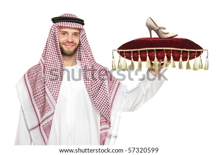 An arab person holding a pillow with a shoe on it isolated on white background - stock photo