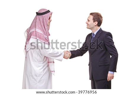 An Arab person shaking hands with a businessman - stock photo
