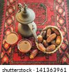 An arabic coffee pot and dates - stock photo
