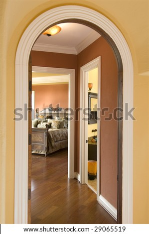 an arched hallway goes into a lush bedroom - stock photo