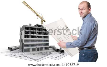 An architect, a building in construction, and blueprints - stock photo