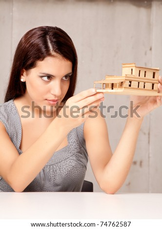 An architect designer examining a rough model house of wood - stock photo