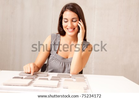 An architect / designer talking on the phone choosing a stone tile - stock photo
