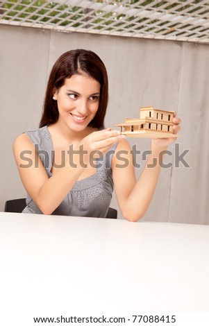 An architect happy with a model house design - stock photo