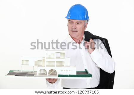 An architect holding a miniature. - stock photo