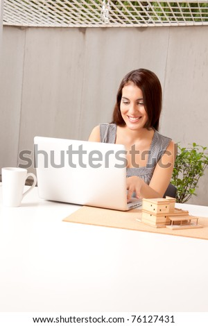 An architect using a laptop computer with a model house on the desk - stock photo