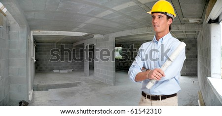 An architect with a roll of blueprints inside a house in construction - stock photo