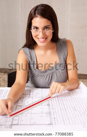 An architecture checking measurements on a set of blueprints - stock photo