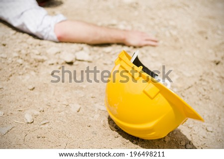 An arm and hard hat lying in dirt. - stock photo