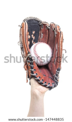 An arm stretches out to catch a baseball using a worn leather glove.  - stock photo