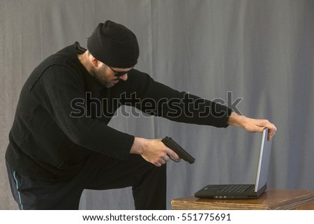 An armed man with a gun and a computer.