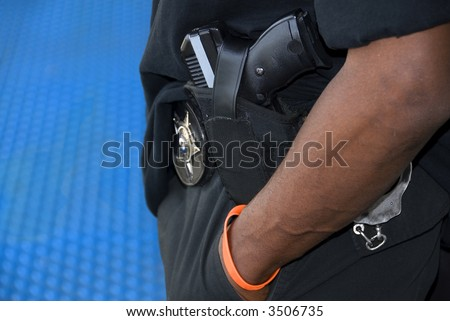 An armed patrolman stands on a platform in a North American transit station. - stock photo