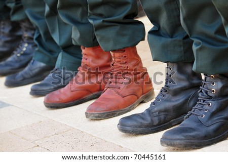An army soldier wears brown boots while all other soldiers wear traditional black boots while participating in a military parade - stock photo