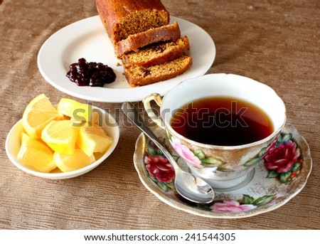 An arrangement of a tea cup, dish of diced lemons and sliced bread and jam. - stock photo