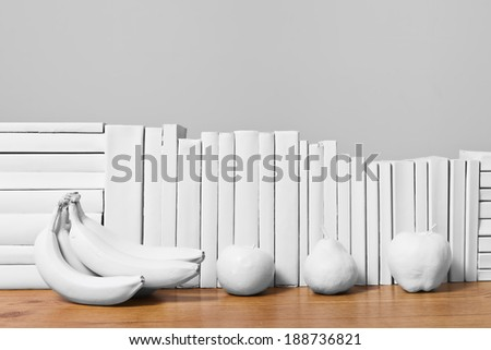 An arrangement of all white books on a wooden table with painted white fruit against a light grey background.