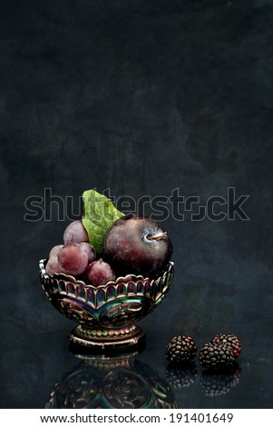 An arrangement of dark fruit and berries with a dark background and reflection. - stock photo