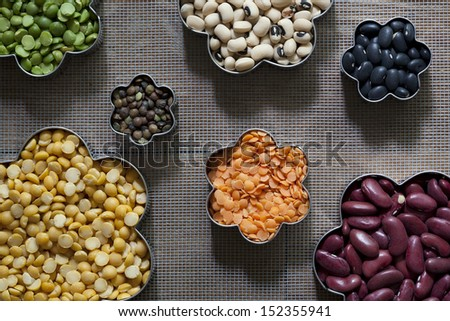 An arrangement of 7 different dried legumes used in the making of various dishes. - stock photo