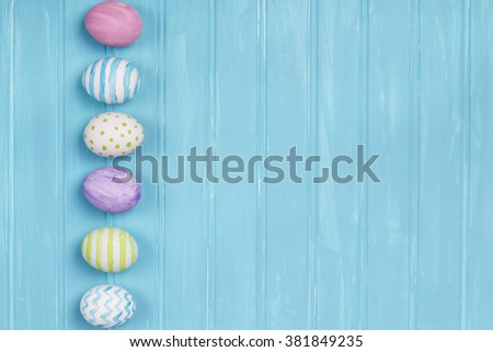 An arrangement of Easter eggs on a turquoise wooden background - stock photo