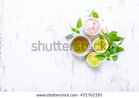 An arrangement of olive oil, himalayan salt, basil, lime and lemon - stock photo