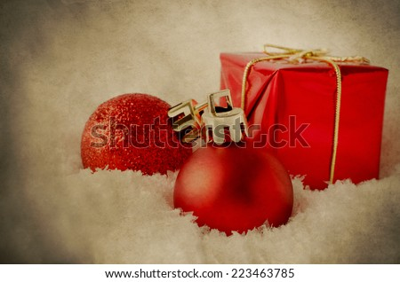 An arrangement of red Christmas decorations sinking into soft, white artificial snow. Processed to give a weathered, grungy, vintage appearance. - stock photo