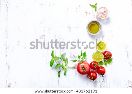 An arrangement of tomatoes, basil, olive oil and himalayan salt - stock photo