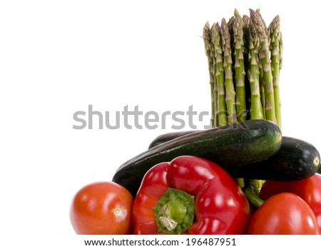 An arrangement of tomatoes, pepper, zucchini and asparagus. - stock photo