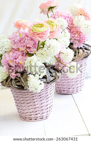 An arrangement of two baskets of spring artificial flowers on white wood - stock photo