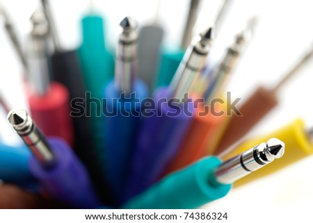 An array of colorful 1/8 inch patch cords with very shallow depth of field. - stock photo