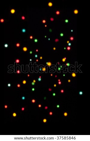An array of different size out of focus fairy lights against a black background, great as a Xmas backdrop. - stock photo