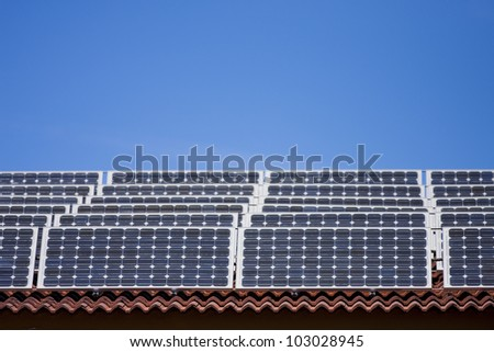 An array of solar panels on a roof, with blue sky - stock photo