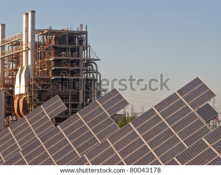 An array of solar panels with a power plant in the background - stock photo